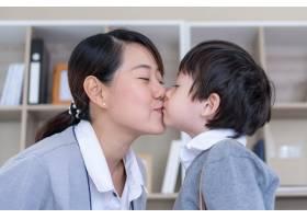 年轻的母亲高兴地带着小男孩在卧室里亲吻她_5388979