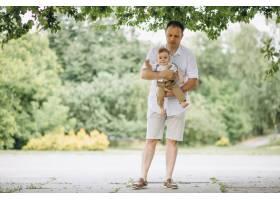 年轻的父亲带着年幼的儿子在公园里_5495201
