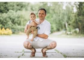 年轻的父亲带着年幼的儿子在公园里_5495202
