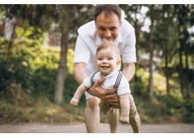 年轻的父亲带着年幼的儿子在公园里_5495206