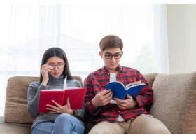 年轻的美女和帅哥坐在沙发上看书_5392723