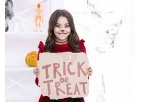 微笑的年轻女孩拿着不给糖就捣蛋的牌子_5499468