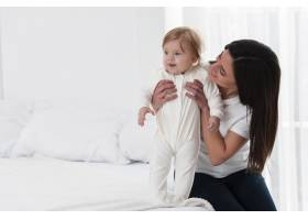 快乐的母亲在床上抱着孩子_6071172