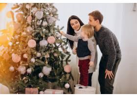 带着小儿子装饰圣诞树的年轻家庭_6426578