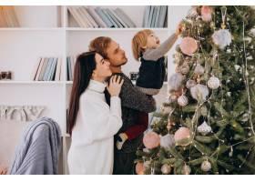 带着小儿子装饰圣诞树的年轻家庭_6426579