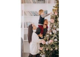 带着小儿子装饰圣诞树的年轻家庭_6426580