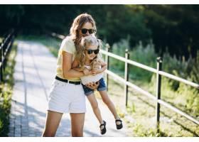 带着小女儿在公园散步的年轻女子_5495949