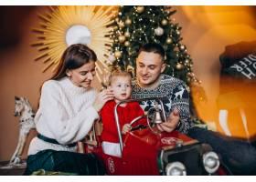 带着小女儿的一家人在圣诞树旁送圣诞礼物_6190858
