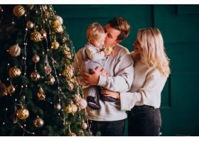 带着小女儿的年轻家庭在圣诞树上挂玩具_6426681