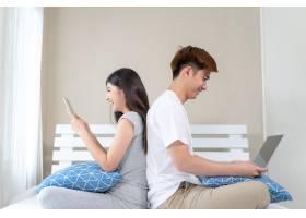 年轻夫妇在床上使用科技设备_5389036