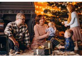 圣诞夜一大家子人在圣诞树旁送礼物_6426559