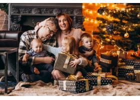 圣诞夜一大家子人在圣诞树旁送礼物_6426560