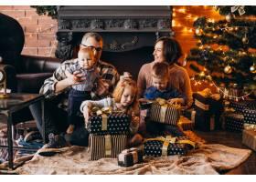 圣诞夜一大家子人在圣诞树旁送礼物_6426561