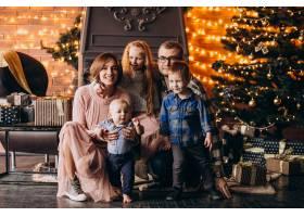 圣诞夜一大家子人在圣诞树旁送礼物_6426566