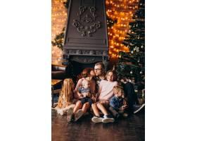 圣诞夜一大家子人在圣诞树旁送礼物_6426571