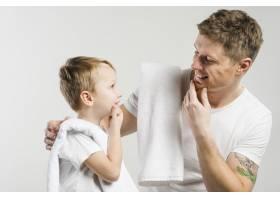父子俩在白色背景下用手触碰下巴的特写镜头_4173754