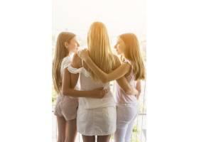 母亲和两个女儿在阳台上拥抱_3991618