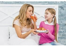 母亲和女儿在床上喝果汁_4029887