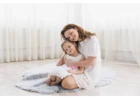母亲和她的女儿坐在家里毛茸茸的地毯上的前_4048394