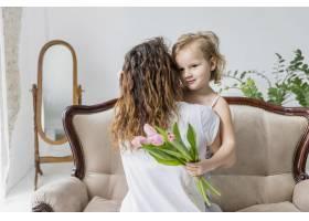 母亲在家里的沙发上抱着粉色郁金香花给女儿_4048248