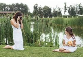 母亲在湖边给女儿拍照_4962111