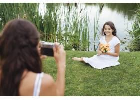 母亲在湖边给女儿拍照_4962114