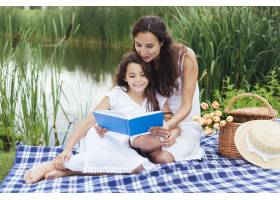母亲在湖边给女儿读书_4962121