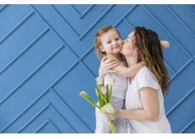 母亲在蓝色的背景上抱着郁金香花亲吻她美丽_4048380