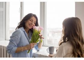母亲带着郁金香女儿站在窗前_4105376