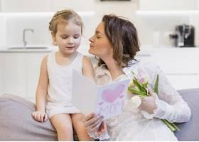 母亲手持贺卡和花束亲吻她可爱的小女儿_4040503