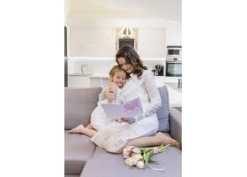母女俩在家里的沙发上一起看贺卡_4057011