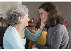 幸福的老母亲抚摸着漂亮女儿的脸_4166899