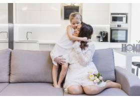 幸福的母亲在客厅的沙发上拥抱着她可爱的小_4057009