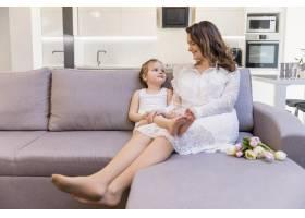 幸福的母女俩坐在家里的沙发上看着对方_4056989