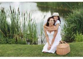 幸福的母女在湖边摆姿势_4962098