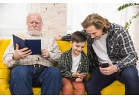 多代男性花时间在一起浏览书籍和智能手机_4361457