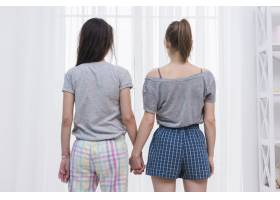 女同性恋夫妇手牵手看白色窗帘的后视镜_4361089