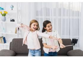 女性朋友在客厅用智能手机自拍的特写_4105373