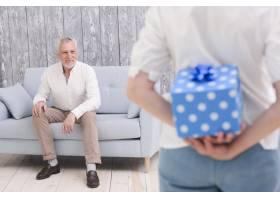 一个女人把礼品盒藏在她幸福的丈夫面前坐_4929753
