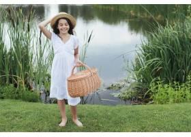 一个女孩拿着野餐篮子在湖边摆姿势_4962078