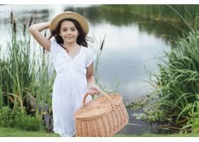 一个女孩拿着野餐篮子在湖边摆姿势_4962080