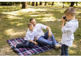 一个小男孩在给他的兄弟和父亲拍照_5149450