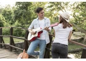 一个年轻人给他的女朋友弹吉他_5022777