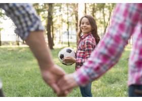 一个拿着足球的女孩在公园里看着她的父母牵_4975795