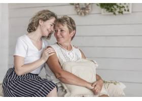 一个迷人的女人和她的母亲坐在沙发上看着对_5043981
