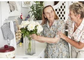 一位高龄妇女手持白色花瓶站在女儿身边_5061058
