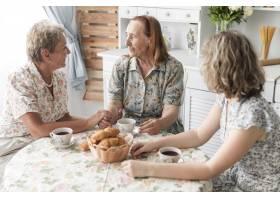 一名妇女在家中与她的母亲和奶奶共进早餐_5043988