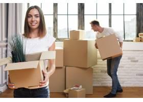 一名妇女拿着一个装有植物的纸箱_5240924