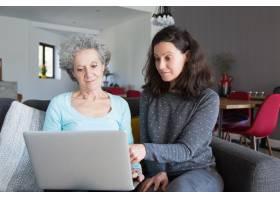一名年轻女子向奶奶讲解如何使用笔记本电脑_4167393