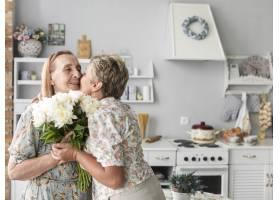 一名成熟女子在家中亲吻手持白色花束的母亲_5061059